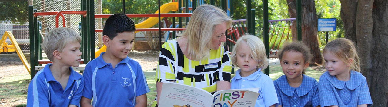 Reading The first day book with some children on a playground bench